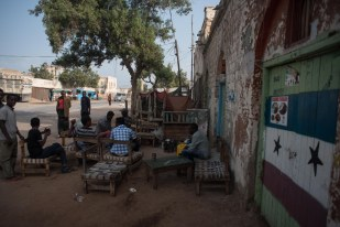 Men drink tea outside a block of colonial era buildings said to have been built by Yemeni Jews. (© Jason Patinkin / The Messenger)